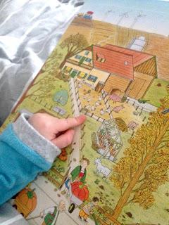 Das Kind zeigt auf ein Huhn im Wimmelbuch