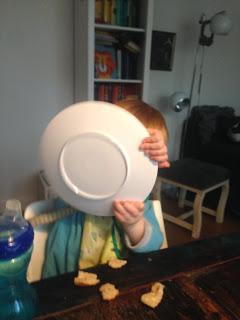 Das Kind spielt mit dem Teller Autofahren Lenkrad