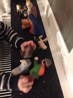 Kind spielt mit den Figuren der Kinderkrippe von Ostheimer