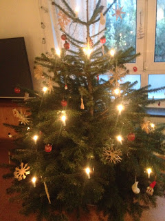 Weihnachtsbaum mit kleinen, roten Äpfeln und Strohsternen und künstlichen Kerzen
