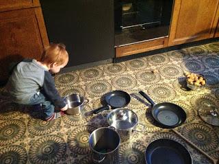 Kind räumt die Küchenschränke aus: Töpfe, Pfannen, Kochlöffel