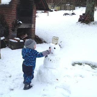 So viel Schnee: Das Kind baut seinen ersten Schneemann und steckt ihm eine Möhre als Nase an.