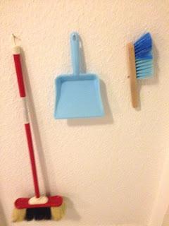In der Kinderecke hängen Besen, Kehrblech und Handfeger für die Hausarbeit