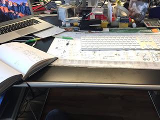 Schreibtisch mit Büchern und Tastatur, Stiften und Blättern