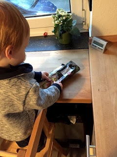 Das Kind möchte Nudeln kochen und nimmt sie aus der Verpackung.