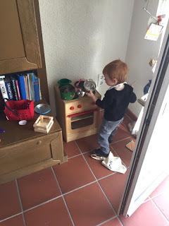 Das Kind spielt in der Kinderküche und hinterlässt etwas Chaos