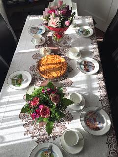 Geburtstagskaffeetisch mit Blumen, Apfelkuchen, Kaffee, Kakao und Sahne