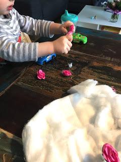 Das Kind steckt kleine Plastikblumen in die Baumwollwatte