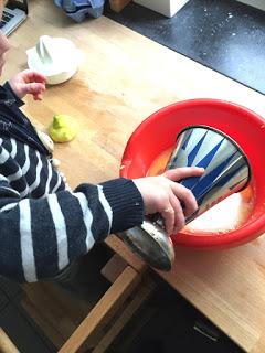 Das Kind fügt das Mehl zum Teig hinzu