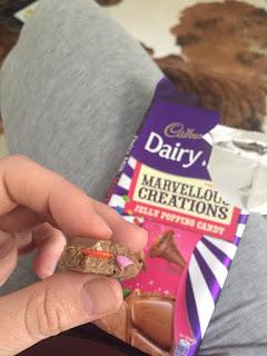 Wir testen Cadbury Dairy Milk Marvelous Creations Jelly Popping Candy: Ein Stück zeigt den versteckten Inhalt.