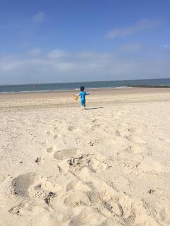 Das Kind rennt über den Sandstrand zum Meer
